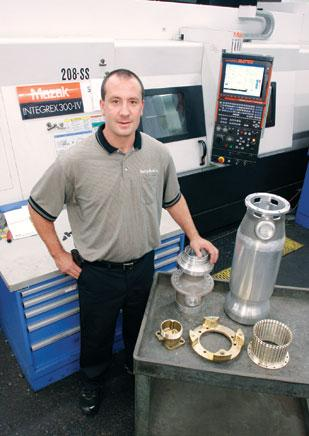 Quality Mould Inc. President D.J. Dunker stands with items produced on the company's Mazak Integrex 300 II Y multiaxis CNC machine. The machine was purchased for $500,000.