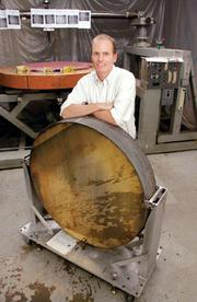 Paul Nacin, owner of Hampton Controls in Wendel, stands behind a large reference collimating mirror that was used for testing in the production of optics for the South Korean government.