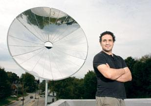 Tom Joseph, CEO of Epiphany Solar Water Systems, stands before a parabolic concentrating dish that is used to focus sunlight and use the energy for water purification.