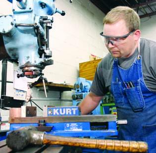 Carl Bean, a tool and die maker at JATCO Machine & Tool Co. in Bellevue, sets up a milling machine.