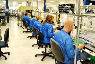 Workers make circuit boards at TMG Electronics Inc., one of three companies under the umbrella of MBG Technologies Inc.