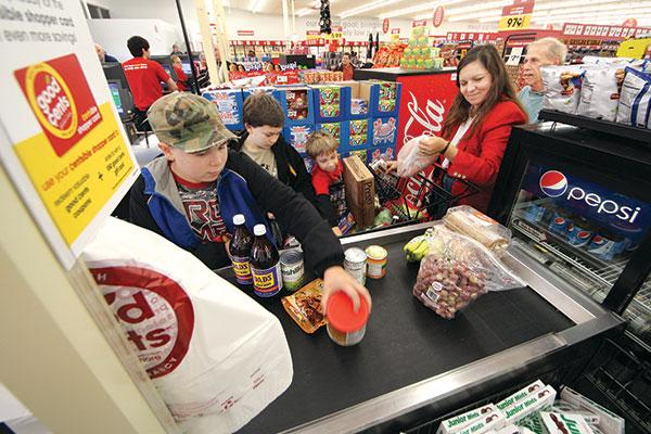 "John and Tina Swanson of Gibsonia receive help from their sons, from left, Josh, Jeff and Josiah with unloading a shopping cart at Good Cents on McKnight Road in Ross Township. ""The family usually grocery shops in Gibsonia,"" John Swanson said. ""We saw the prices were really good. With a family a five, these guys eat."""