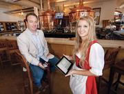 Thus far, Birchmere's new fund has invested in two local companies, including NoWait. CEO Robb Myer is pictured above with Hofbrauhaus hostess Alysia Umbaugh holding different versions of the NoWait restaurant tool.