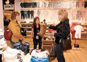 Kim Harmon, right, of McKeesport is assisted by her friend, Elaine Phillips, left, and sales associate Maureen Nellis. Harmon was shopping for her grandson at 77 Kids by American Eagle in the Ross Park Mall.