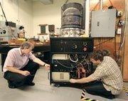 John Shea, left, and Jason Carrodus conduct tests on a vacuum deposition chamber in Eaton's plasma physics laboratory.