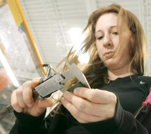 Angela Bontrager uses a caliper to inspect an injection-molded military helmet clip at Pasco Tool & Plastics Inc.