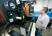 Todd Walsh operates a wire Electrical Discharge Machine, which uses .010 brass wire to burn steel.
