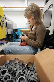 Linda Hill inspects a plastic component.