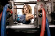 Tanya Gosnell inserts a component to be overmolded into a Milacron injection molding machine