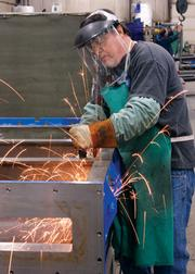 John Gamble grinds a vacuum chamber at Alle-Kiski Industries in Leechburg.
