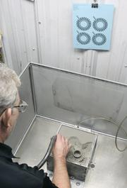 3. A technician clears away unused material. Unused powder can be reused.