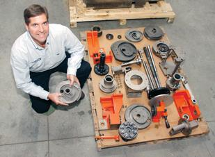 Kirk Larimer, VP and general manager at Jennison Quality Components Inc., kneels next to some parts from a pill machine.
