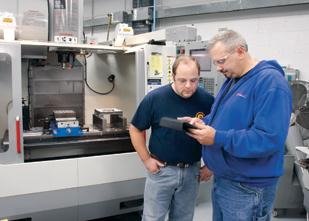 Shop supervisor Dave Smathers, right, and shift supervisor Josh Campbell use an iPad to download a five axis CNC program from the machine to the company's file server at L&S Machine CO. LLC in Latrobe, Westmoreland County.
