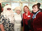 Santa Claus (Herb Dankmyer), left, Kathleen Seaton, Cindy Parknavy and Allyson Sveda enjoy the Hawaiian Christmas-themed Presents for Patients Victory Celebration party held at the Crystal Conservatories at St. Barnabas.