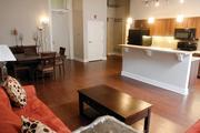 A staged living area, dining area and kitchen in this two-bedroom apartment at Residences at South High.