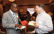 Carlos Carter, left, of Bank of America Merrill Lynch chats with Andy Carlton of The Pursuit Group.