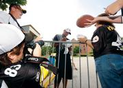 Former NFL player Dwight Smith autographs a football for a fan.
