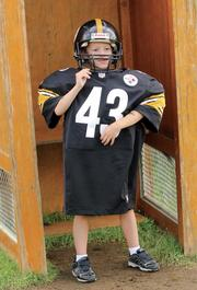 Liam Nierle of Biddeford, Maine, poses for a photo in Pittsburgh Steelers equipment Aug. 1, 2012 in the Steelers locker room stall display at the UPMC Steelers Experience, the team's interactive theme park located near football practice fields at Saint Vincent College in Latrobe, Westmoreland County. Liam was with his father, Pat, who grew up as a Steelers fan in Moon Township.