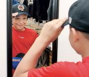 Tim Lapp, 11, of McMurray, checks the fit of a Washington Wild Things cap in the team store at Consol Energy Park before a game against the Evansville (IN.) Otters July 18, 2012. Lapp was attending the game with a youth group from Trinity United Methodist Church.