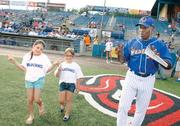 Washington Wild Things assistant coach Lenny Randle jokes with honorary bat kids Gwen Havern, left, of Swisshelm Park and Bella Santoro of Canonsburg as they make their way to home plate to present the starting line-ups to umpires before the Wild Things game July 5, 2012, with the Rockford (IL.) Riverhawks. Randle's professional baseball career has spanned almost 17 years, including 11 in the Major Leagues.