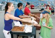 """Elana Williams, the 20-year-old daughter of Washington Wild Things majority owners Stu and Frani Williams, hands out cookies July 5, 2012 during the popular """"cookies and milk"""" sale which is held in the middle of the fifth inning at each home game. Elana has been working in some capacity at the ballpark since she was 15. """"It's a family business,"""" she said."""