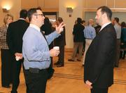 Eric Booth, left, of Desmone & Associates Architects chats with featured speaker Christopher Flickinger of Dale Carnegie Systems.