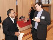 Arun Thomas, left, of Eckert Seamans chats with Stephen Morrow of Boston Consulting Group.