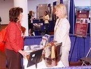 Sandy Funk, left, of Fairmont Supply speaks to Patti Dittman of Millcraft Industries.