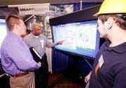 Robert McKinley of SMARTSolution Technologies demonstrates a product to Dan Talbert of Tradesman International.