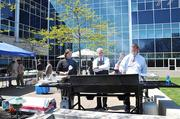 Josh McElhattan, director of business development; Kent McElhattan, chairman and co-founder; and Justin McElhattan, president and CEO, grill burgers for an Industrial Scientific cookout held to raise money for Scouting for Food.