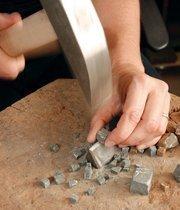 Sager Lynch uses a traditional hammer and hardi to cut stone.Photo by Joe Wojcik.