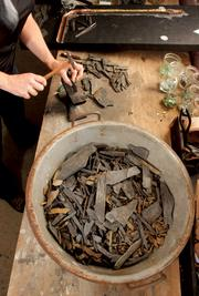 Sager Lynch uses a watchmaker's hammer and mini anvil to shape genuine Marcellus Shale.Photo by Joe Wojcik.