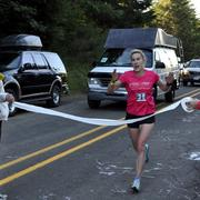 A runner crosses a makeshift finish line after cresting the notorious Leg 31 hill in the Coast Range.