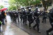 Riot police patrol a downtown Portland street, readying for the Occupy May Day marches.