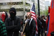 Masked Occupy May Day protesters hold flags during Tuesday's demonstrations.