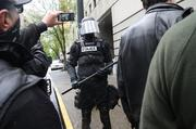 An Occupy May Day protester takes video with a flipcam of a riot policeman.
