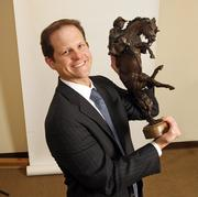 Justin Sawyer, litigation partner for Miller Nash LLP. Sawyer keeps this statue, which his father won for his own trial law accomplishments, in his Miller Nash office.