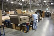 A Pacific Furniture Industries worker puts the finishing touches on a couch.