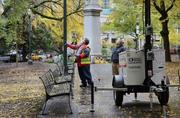 A Portland Parks & Recreation Department official assesses damage to a light pole Monday at downtown Portland's Lownsdale Square a day after city police cleared the park of the Occupy Portland encampment.