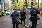 Portland police officers, still clad in riot gear, continue to patrol the downtown parks a day after clearing out the Occupy Portland encampment.