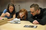 Carrie Dimoff, a footwear developer on Nike's running products team, explains to Autumn and her father, Billy Boynton, how she can customize the Nike Air Max 90. Autumn was given the blank model shown here to sketch out her ideas.