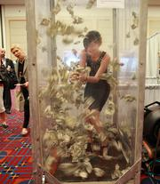 Portland Community College student Alexandra Richards attempts to grab cash blown around as part of a game featured at the booth hosted by PCC's CLIMB Center for Advancement.