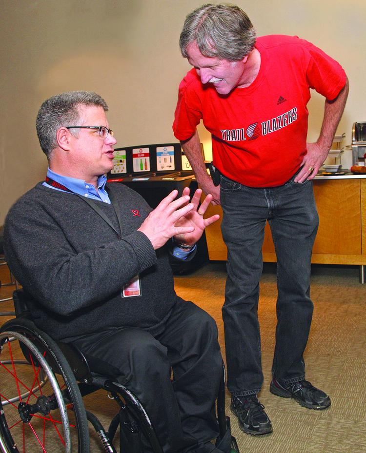 Ian Jaquiss, left, talks with Blazers fan Pat Maguire during Monday's game.