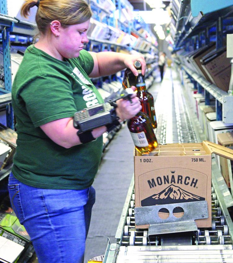 OLCC employee Tracy Floslie repackages Oregon-made spirits into recycled boxes.