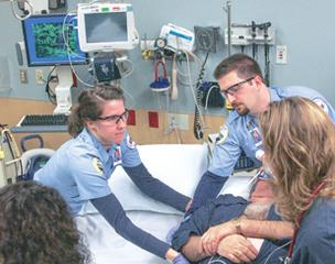 Personnel from American Medical Response and Adventist Medical Center attend an emergency room patient.