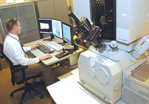 FEI tech sales manager Craig Henry works alongside one of the company's Helios NanoLab microscopes.
