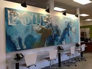 A mural at 3fold Communications features California's state animal, the grizzly bear. The long table underneath features phones and a work space for guests. At any time during the day, at least two visitors are using the space.