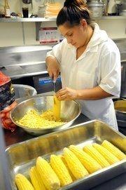 Karely Farrera cuts corn off the cob in the kitchen of Sacramento's Biba Restaurant.