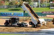 A truck unloads a pile of dirt in preparation for a monster truck rally in West Sacramento. It took 20 trucks making 166 trips to fill the area with dirt.