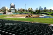 Workers spread dirt across plastic to protect Raley Field. It took 20 dump trucks making 166 trips to the baseball field to bring enough dirt for the recent monster truck rally.